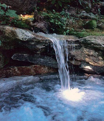 Natural stone hot tub with waterfall. Yes please!